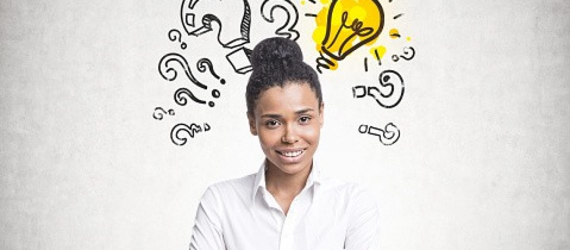Smiling confident young African American woman wearing a white shirt and black pants standing with crossed arms and looking at the viewer. Question marks and a light bulb on a concrete wall